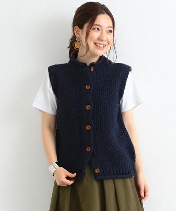 ウッド調のボタンに鹿の子編みが温もりあるベストは手編みのお品。シンプルな白いTシャツを合わせても可愛らしく、秋口から活躍してくれそう。
