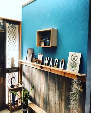 鮮やかなブルーがインパクト大の玄関。手作りの棚でスペースをオシャレに有効活用しています。