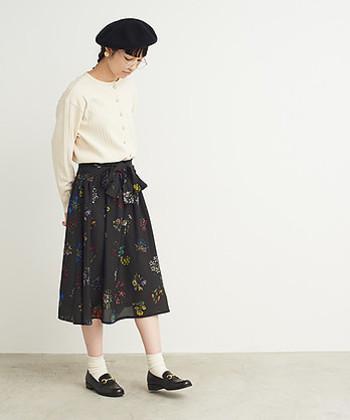 黒の花柄のちょっぴりクラシカルな膝丈スカート。カーディガンと白ソックス、丸眼鏡で文学少女のような雰囲気に。