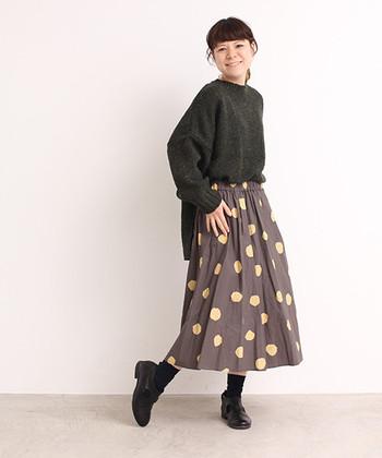 こげ茶のスカートに大きなトッド柄スカート。トップスと足元を黒でシンプルに合わせて。秋冬にも温かさを感じるコーデですね。