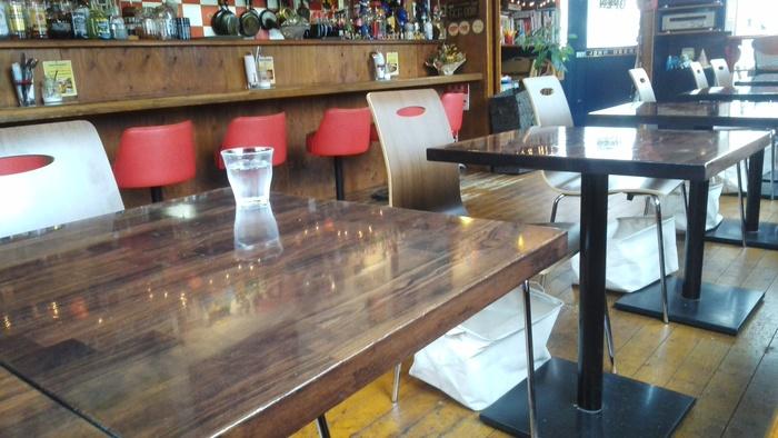ダークブラウンのテーブルと赤い椅子がおしゃれな店内。ちょっぴりレトロでアメリカンな雰囲気です。
