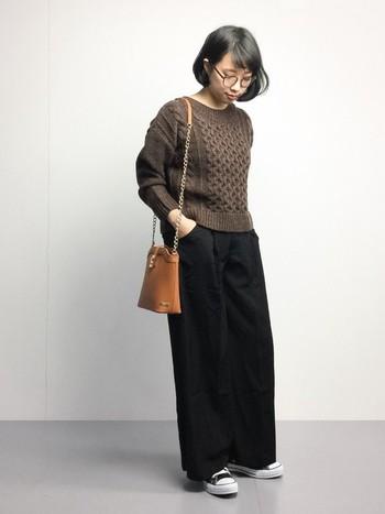 ココアやチョコレートのような深みのあるチョコブラウン。ブラックとの合わせは鉄板です。  ケーブル編みが可愛いニットに黒のワイドパンツのシンプルなコーデ。足元をスニーカーにして抜け感を出し、キャメルのショルダーで女性らしさをプラス。秋のお散歩に調度いいリラックススタイルに。