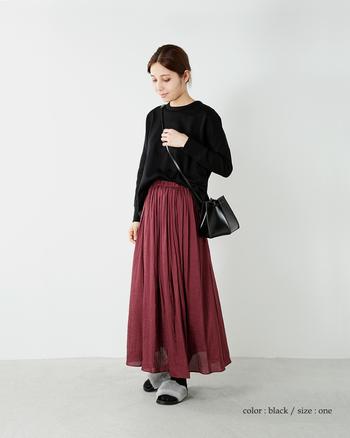 ころんとしたフォルムが印象的なのは、底の部分が六角形になっているバッグ。巾着のようにきゅっと絞るデザインになっており、新しさの中に使い慣れたような懐かしさも感じられます。ワインカラーのフレアスカートが、さらに上品に見えますね。
