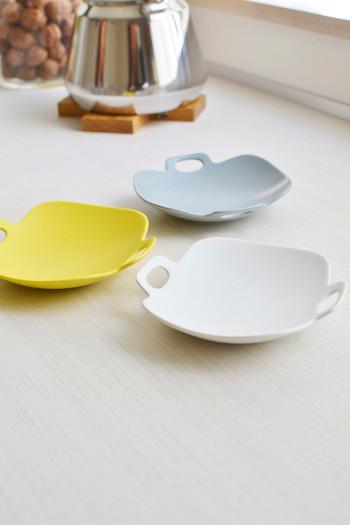 """""""手作りとプロダクトの境界線にあるもの""""をコンセプトに、日々の暮らしに馴染む素敵な器づくりを手掛けている磁器作家のイイホシユミコさん。磁器ブランド「yumiko iihoshi porcelain(ユミコ イイホシ ポーセリン)」の食器は、ほっと心がなごむ温かみのある佇まいと繊細な色使いが特徴です。写真のプレートは、""""旅に持っていく器""""をテーマにした 「bon voyage(ボンボヤージュ)」シリーズ。食器をヒモで縛って旅先に持っていけるようデザインされた""""耳""""が、とっても愛らしい雰囲気です。"""