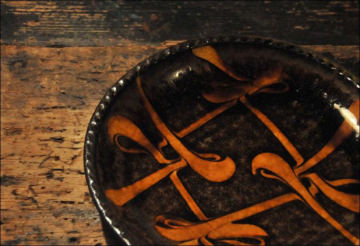 スリップウエアは、民芸運動で有名な濱田庄司らがイギリスから持ち帰ったもので、その後、日本独自に発展していきました。化粧土を入れたスポイトで描くことで独特のタッチが生まれ、色は茶系がほとんどで、厚ぼったいのが特徴です。