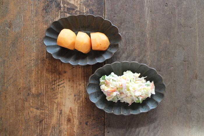 マーガレットの花をイメージしたマットな質感の深皿。見る角度によって違う、落ち着いたチャコールグレイの渋みが、素朴な柿を引き立ててくれます。