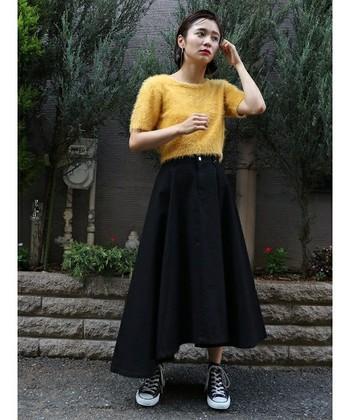 黒のチノスカートと鮮やかなイエローのモヘアのニットと合わせた、甘辛ミックスコーディネートは、異素材や色のコントラストが印象的です。