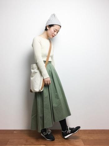 グリーン系のチノスカートとホワイトニットの優しい色合いのコーデは、グレートーンのスニーカーに黒のタイツを合わせて引き締めて。