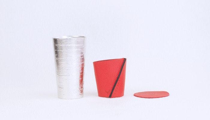 本錫100%の能作のビアカップはビールを注いだとき、カップ内側の砂目の仕上げにより、きめ細やかな泡の層ができます。ビアカップだけでなく、カップの中の飲料の熱や冷えから手を守ってくれるスリーブに、同色のコースターの3点セット。スリーブとコースターの素材は、植物タンニンなめしのエゾシカ革を使用しているので、使うほどに色が濃くなり、艶が出てきて味わいが増してきます。