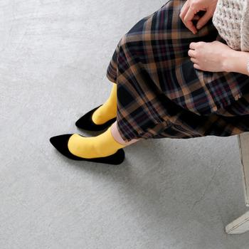 シックなチェック柄のスカートスタイルに、タンポポイエローのカラーソックスを合わせたコーディネート。たまにはカラフルに冒険してみませんか?