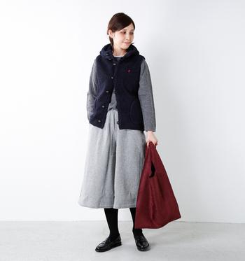 Gymphlexの「くるみボタンボアベスト」を、アウターとして使っているコーデです。グレートーンで合わせた服に、黒色のダウンベストと赤色のバッグをプラスすることで、暗い印象になりがちなグレーコーデを盛り上げています。
