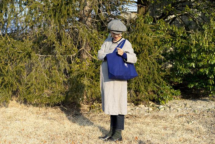 パッと目を引くブルーのトートバッグは、デンマークのスーパーマーケット「Irma(イヤマ)」オリジナルのトートバッグです。グレージュのワントーンコーデにメリハリを持たせてくれます。