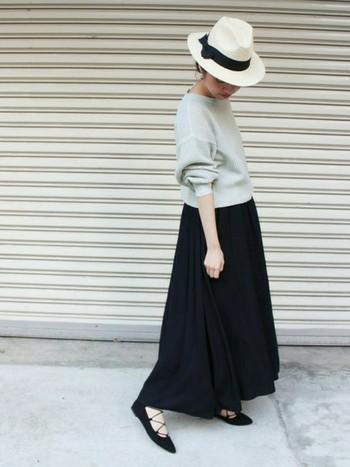 グレーのニットにマキシ丈のチノスカートを合わせて。黒のレースアップパンプスとハットで、上品に着こなしたスタイルです。