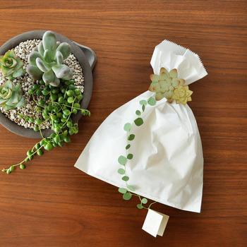 よく見かける白い紙袋をキュッと束ねてモチーフを飾って。観葉植物好きなら多肉植物、猫好きなら猫モチーフ。贈る人の好みに合わせてモチーフを考えるのも楽しそうです。