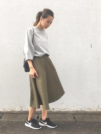 グレーやカーキを使ったシンプルなスカートスタイルに黒のスニーカーを合わせて。バッグなど小物と同色にして、色数を抑えるのも大人っぽく見せるポイントです。