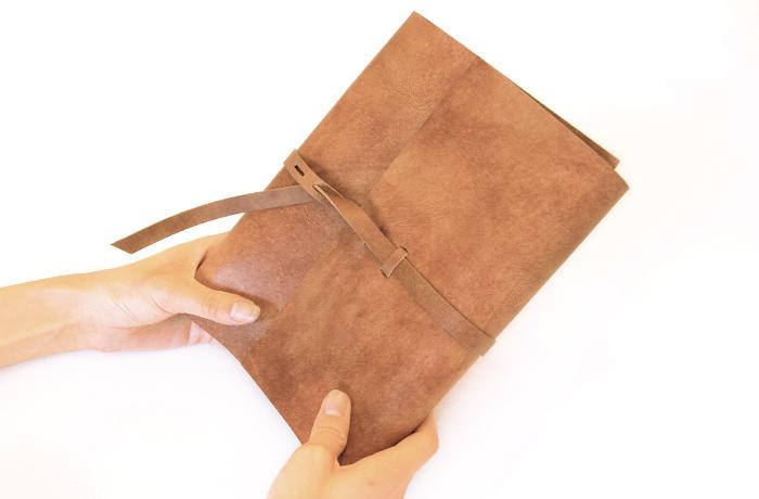 使うほどに手に馴染む、やわらかな一枚革をひもで巻き込むデザインのシステム手帳。手にしっとりと吸い付くような素材の上質感に加え、デザインのラフさが魅力。