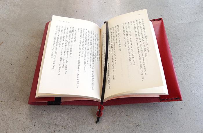 見開き左側が折り返し革なので、かなりの厚みの本まで対応できます。はじめは革の張りがあり、やや浮いて見えますが、本の重みで徐々に折り返しがくっきりとしてきます。しおり紐も共革で、飾りボタンがキュートなアクセントに。