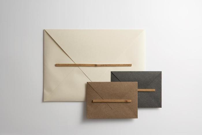 『竹綴じ封筒 S/L 』  フタを竹に潜らせて留める、強度のある封筒。風呂敷のイメージで、直線にカットした紙を手貼りで仕上げています。胡麻竹を一本ずつナタで割り、程よい厚みに削っています。足袋のこはぜを留めるような、日本人特有の丁寧な所作をデザインに取り入れました。