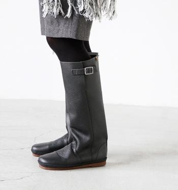 Koosのベルト付きロングブーツ。柔らかで上質な天然皮革と大きめのステッチが、あたたかな雰囲気を醸しています。エンジニアブーツ風のベルトもあしらった、アンティークなイメージのシンプルなロングブーツです。