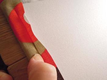 カラーボードの裏側に、カッターで生地を挟み込むための溝を浅めに付けたら、そこに爪で生地を押し込んでいきます。
