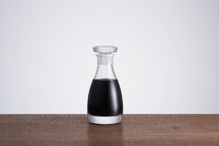 赤い蓋に円錐形ガラスという昔懐かしい醤油差しを基に、素材・容量・サイズの3点も改良を加えています。素材にはガラスの中でも特に透明度の高い「クリスタルガラス」のみを使用することで、プラスチックと篏合させるねじ込みが不要になり、より衛生的ですっきりとした見た目に。容量は醤油の鮮度が落ちないうちに使いきれる80㎖に設定し、高さは113㎜と小ぶりなサイズ感ながらも、底面を厚くすることで倒れにくい構造になっています。