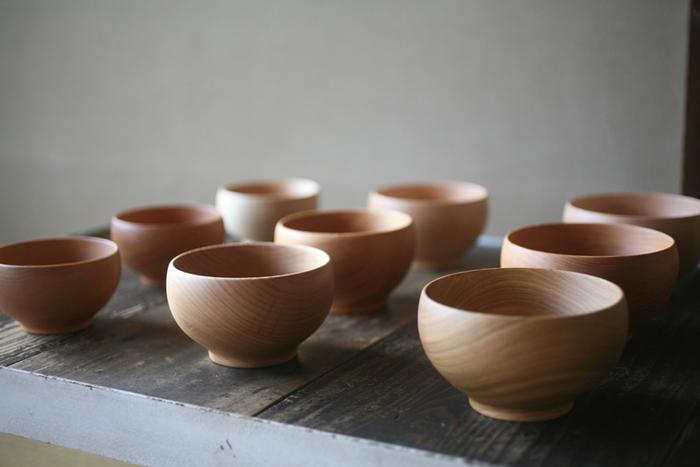 1996年にグッドデザイン賞を受賞した「銘木椀」シリーズは、薗部産業を代表するロングセラー商品のひとつです。木の選別・乾燥・形成・塗装仕上げの全工程を薗部産業の職人が行い、お椀一点が完成するまでに数か月という長い時間を要します。銘木椀に使われている素材は、さくら・けやき・ぶな・くり・くるみ・ならの6種類。同じ種類の木材でも木目や色合いが異なり、一つ一つ違う印象を楽しめるのも魅力です。