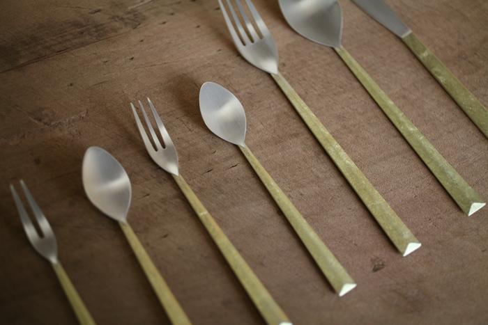 """真鍮と銀のコントラストが美しいFUTAGAMIの「カトラリー」シリーズ。テーブルコーディネートを引き締めるスタイリッシュなデザインと、真鍮鋳肌ならではの心地よい肌触りが特徴です。ぬくもりのある優しい輝きが魅力の真鍮は、使い込むことで現れる""""経年変化""""を楽しむことができる素材です。艶やかなゴールドから渋い色合いへと少しずつ変化し、なんともいえないアンティーク風の独特の味わいが出てきます。"""