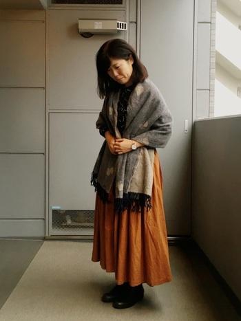 秋らしいビターな印象のオレンジに、ブラウン系のミナ ペルホネンのコラボストールを合わせた秋色コーデ。  衣類を無地でまとめているので、ミナ ペルホネンの「CHOUCHO」デザインが引き立っていますね。