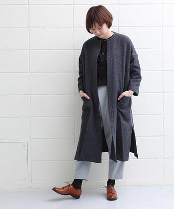 レースアップの革靴はきちんとした雰囲気の装いにぴったりです。ノーカラーのロングコートがショートカットの髪型によく似合っています。