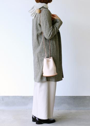 白い巾着型のショルダーバッグは、グレートーンでまとめたコーデに合わせて。季節感を感じさせる、柔らかい印象の着こなしに仕上がっています。