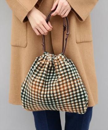 こっくりとしたブラウンやマスタードカラーなどを織り交ぜたチェック柄バック。丸みの巾着バックは、ほっこりレトロな雰囲気たっぷりです。