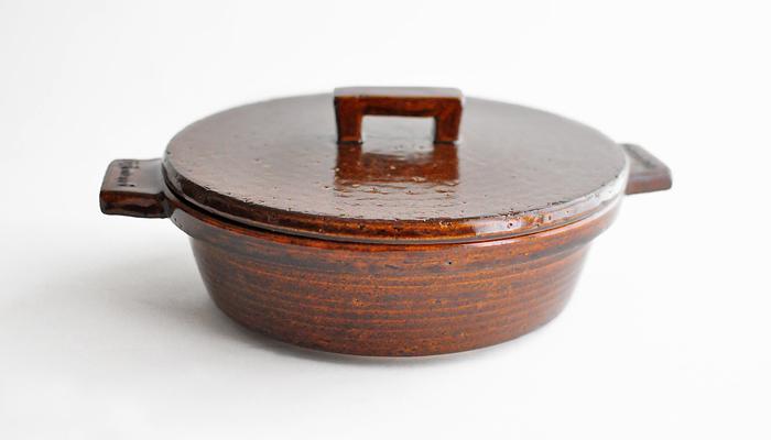 蓋が平らでコンパクトサイズのアメ色のビストロ土鍋。オーブンに入りやすいようにデザインされており、蓄熱製も高いのでお米以外の料理でも使えます。