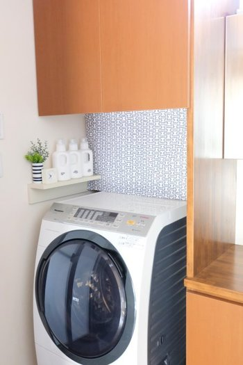 洗濯機横の壁面に付けた、小さな飾り棚。毎日使う洗剤は、こんな風にすぐに使える場所に置いてあると便利です。  さらに、この洗濯機の奥にあるファブリックの目隠しに注目!
