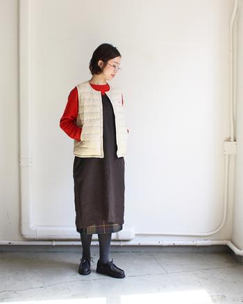 赤を効かせ色に、白のダウンベスト。スカートのチェックも効いています。ちょっぴりロンドンっぽさのあるファッションに、カジュアルさを混ぜ込んで。