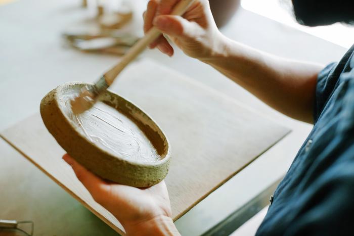 白い土から作られた泥を何回も重ねて塗り、筆のタッチをそのまま残します。この作業が独特の質感の秘密のひとつ。冒頭に登場した水色の器も同じ過程で質感を作り上げます