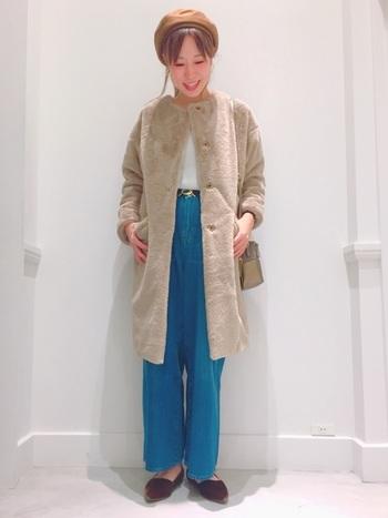 ベージュのファーコートと鮮やかなブルーのパンツを合わせたパンツスタイル。ウールのベレー帽とベロアのシューズのあたたかみのある素材と色で柔らかく引き締めています。