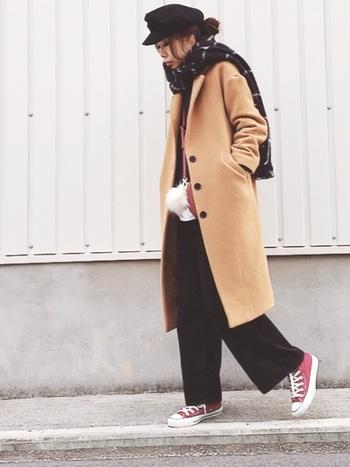 キャスケットやワイドパンツなど黒でまとめたシンプルなパンツスタイルは、ベージュのロングコートやチェック柄マフラーなどで程よくアクセントを。さらに足元は、カジュアルなスニーカーで抜け感をプラス。