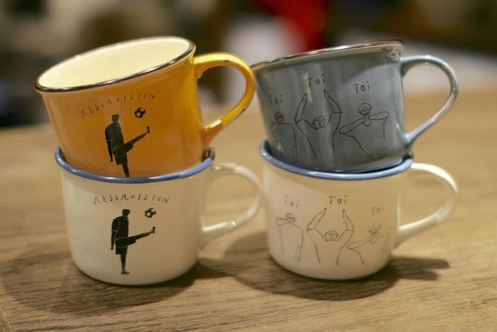 ナガノさんのシュールなイラストが描かれた「MUG CUP」。素敵な色合いの美濃焼きのマグカップに、スタメン待ちでサッカーボールを蹴る人と、toitoitoiと応援する人達が描かれています。ほっこりティータイムが楽しめそうです。