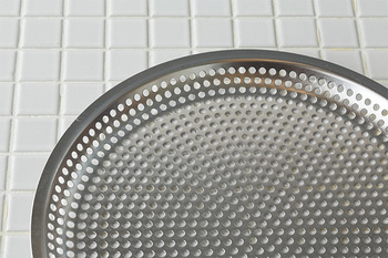 本来、パンチングの穴は周辺部は楕円形に歪んでしまうため、水切りが不均一になりがち。ところが、まかない平ザルのパンチングの穴は、中心部も周辺部もすべてきれいな正円になっています。