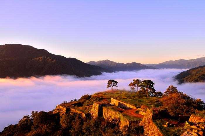 日本100名城の1つ、兵庫県朝来(あさご)市の標高約350メートルの山頂にある「竹田城跡(たけだじょうせき)」。朝霧に取り囲まれると雲海に浮かぶように見えることから「天空の城」とも呼ばれています。朝日に彩られた雲海と竹田城跡は、まさに絶景。
