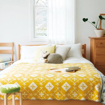 大きなブランケットは、ベッドカバーとして使うのにも向いています。イエローが寝室を明るく見せてくれます。