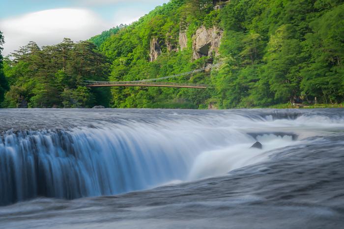 群馬県沼田(ぬまた)市にある、高さ約7メートル、幅約30メートルの「吹割の滝(ふきわれのたき)」。「東洋のナイアガラ」と称され、四季折々の自然の美しさを映す滝は、遊歩道からゆっくり眺めることができます。1936年に天然記念物に指定されました。
