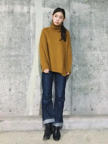 マスタードカラーのタートルネックのセーターとデニムのカジュアルコーデ。ゆったりとしたニットの空気感に合わせて、デニムの裾もゆるっとラフに折り返して。ブーツとのバランスが絶妙です。