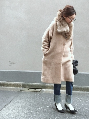 ファーティペットがアクセントになった、寒い季節のフェミニンなデニムスタイル。幅広にロールアップしたきれいめデニムは、靴下×パンプスでちょっぴりレディライクに着こなして。