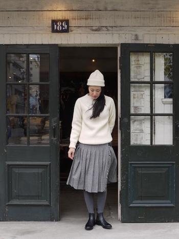 ひざ丈のプリーツスカートに、白のニットを合わせたシンプルコーデ。スカートと同系色のタイツを合わせて季節感を出して。