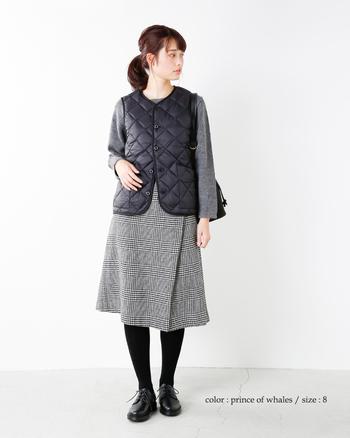 トーンを合わせたセンスのいいコーデ。カジュアルなベストを合わせても、グレンチェックの巻きスカートがクラシカルな印象を残してくれます。