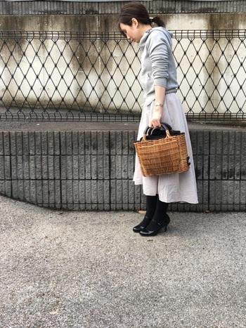 グレーのパーカーとかごバッグでカジュアルな中にも女性らしさが♡冬の定番黒タイツもホワイトのスカートとバッグで軽やかな雰囲気に。