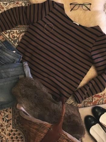 落ち着いたブラウンのカゴバッグに同系色のファー&カットソー。シックな色合いで冬らしい季節感をアップしたカジュアルコーデは、ちょっとしたお出かけに。