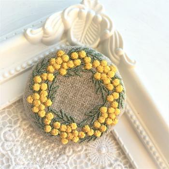 黄色いミモザのリースを刺繍した、美しくてかわいいブローチ。飾っておきたくなるほど素敵な作品です。このブローチをつけてお出かけしたら注目を集めそうですね。