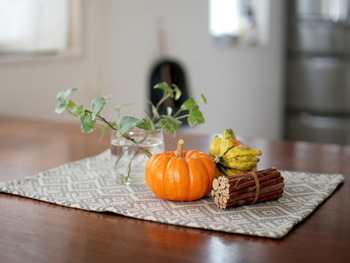 観賞用の小さいかぼちゃは、組み合わせてテーブルに置いても◎ 織り柄のランチョンマットを敷いて、北欧ミックス。